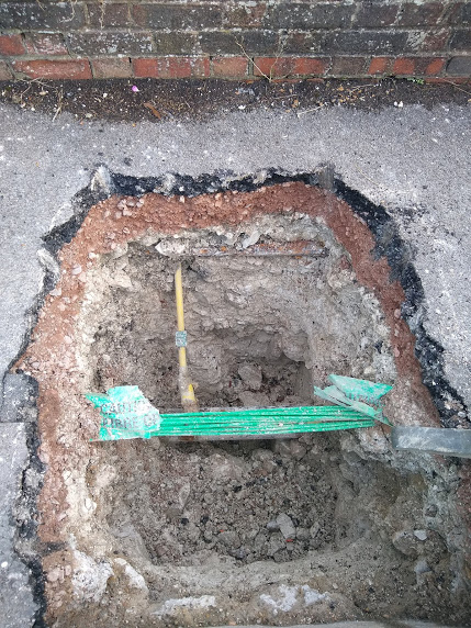 deep hole in the pavement, at the bottom which is a bundle of fibre-optic cables