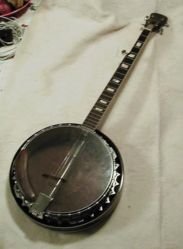 """Photo of a Harmony resonator banjo from the 1960s or 1970s. The head is transparent, the pot is aluminum, and the neck has """"Mother of toilet seat"""" inlays."""