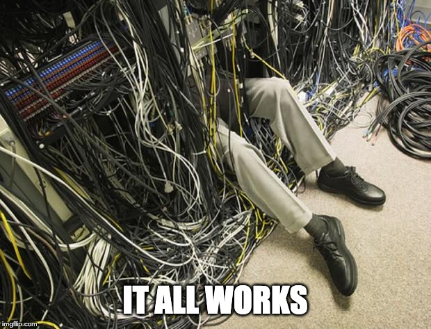 person's legs under complicated wiring with caption It All Works